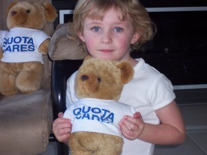 Young child holding her very own Quota Cares Teddy Bear