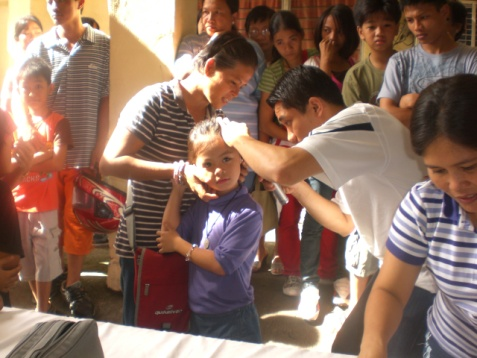 Donita Jison receiving an ear exam thanks to the Quota community in Iloilo, Philippines.