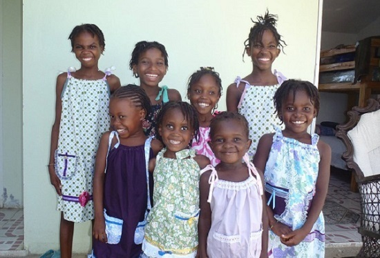 Young girls receive handmade dresses made by Quotarians.